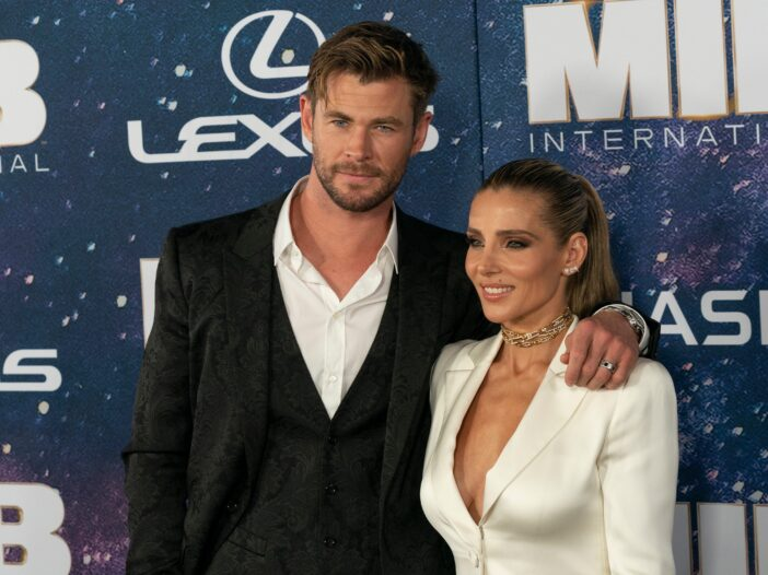 Chris Hemsworth wears a black suit and stands with his arm around Elsa Pataky, in a white suit