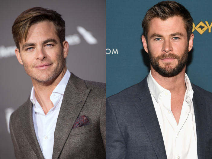 Chris Pine on the left wearing a dark gray-brown suit on the red carpet. Chris Hemsworth on the righ