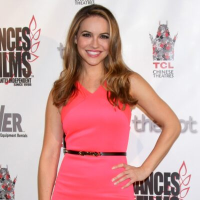 Chrishell Stause wearing a bright pink dress standing against a white background with black words
