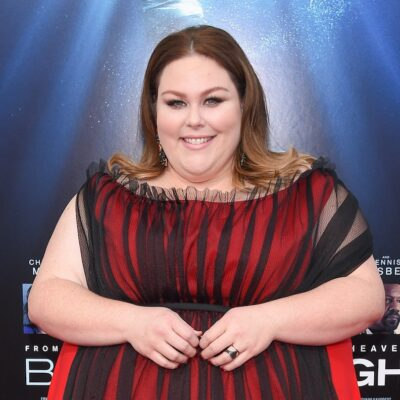 Chrissy Metz smiling in a red and black dress outside against a blue poster