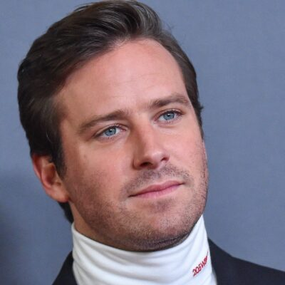 Close up of Armie Hammer in a turtleneck and jacket