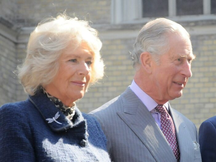 Close up of Camilla Parker Bowles in a blue jacket standing with Prince Charles in a grey suit