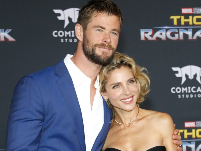 close up of Chris Hemsworth smiling in a blue suit with an arm around Elsa Pataky in a black dress
