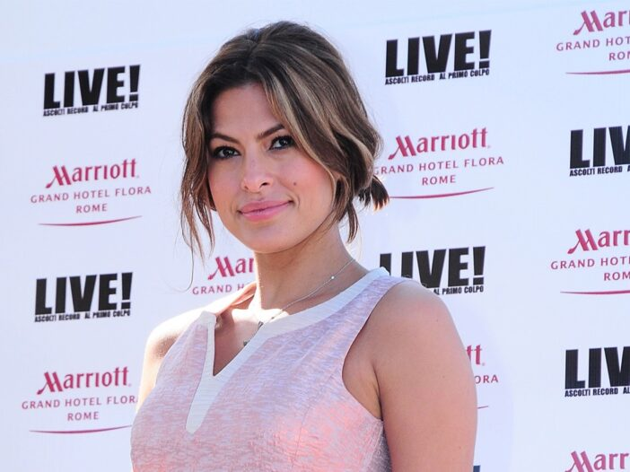close up of Eva Mendes smiling in a pink dress against a white background