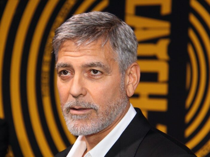close up of George Clooney in a suit looking forward against a yellow background