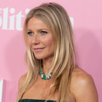 Close up of Gwyneth Paltrow in front of a pink background.