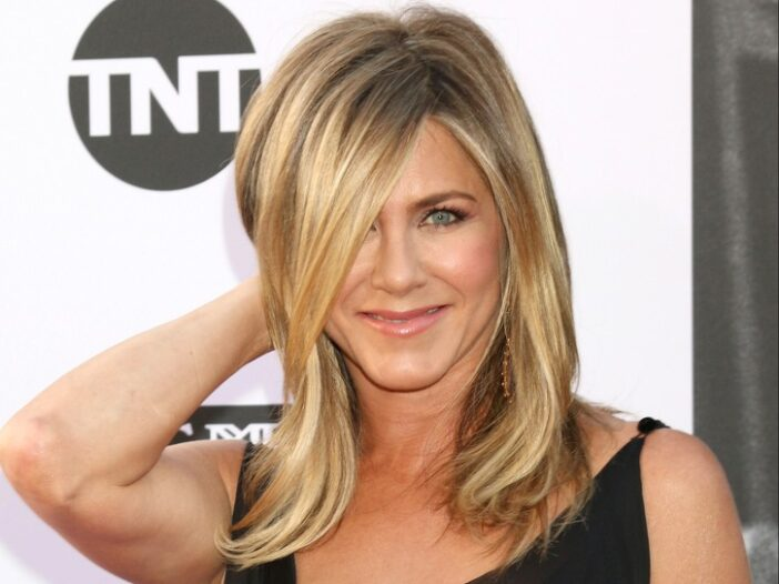 Close up of Jennifer Aniston with her hand behind her head.