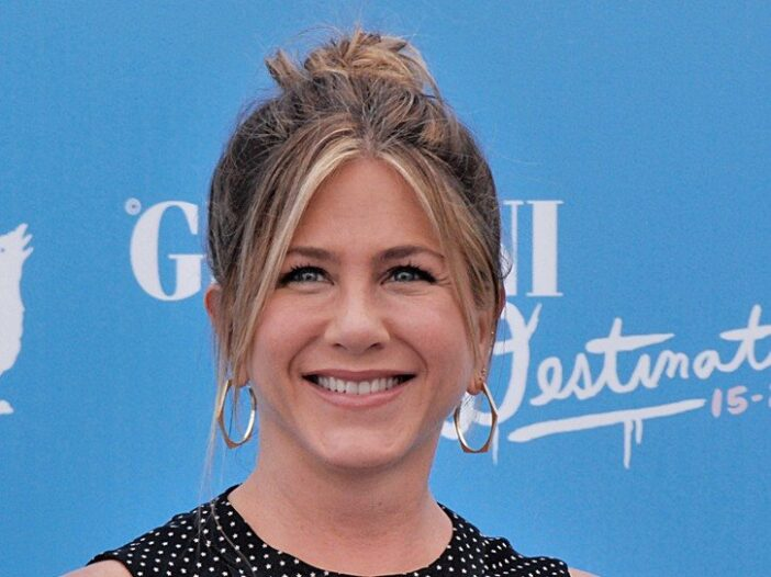 Close up of Jennifer Aniston in front of a blue background.