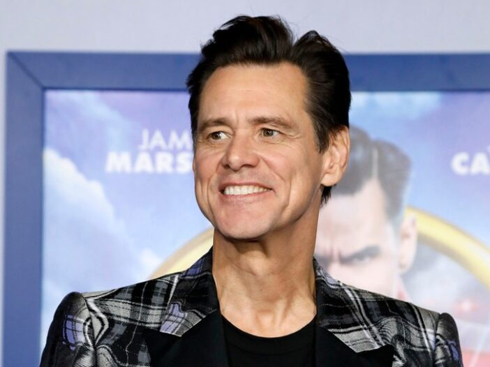 close up of Jim Carrey smiling in a black plaid sports jacket