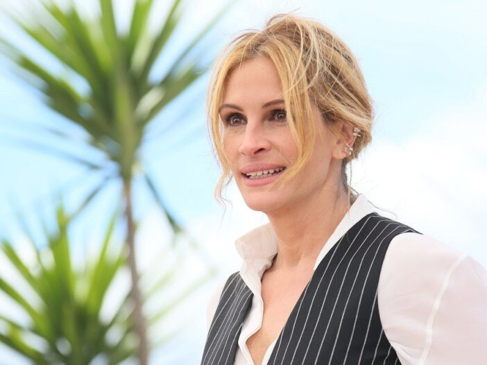 close up of Julia Roberts smiling in a white shirt and black striped vest outside