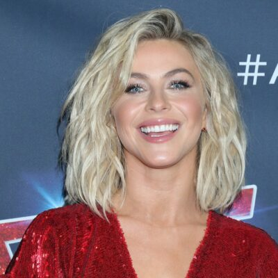 close up of Julianne Hough smiling a red dress against a black background