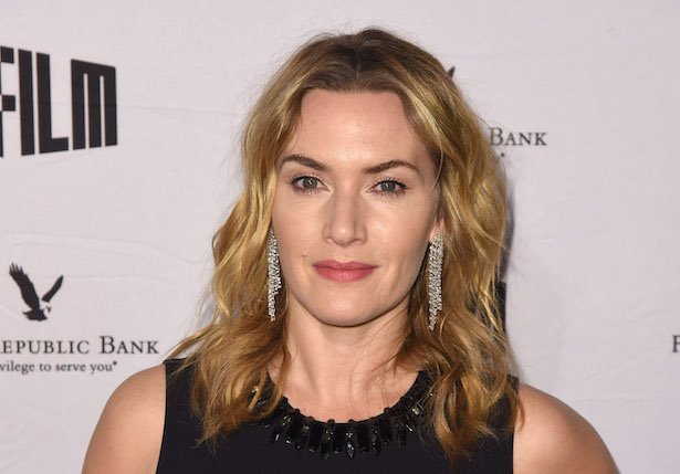 close up of Kate Winslet in a black dress with dangling silver earrings against a white background