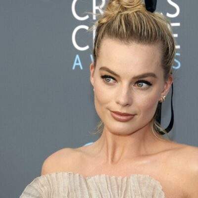 close up of Margot Robbie smiling in a beige dress against a grey background