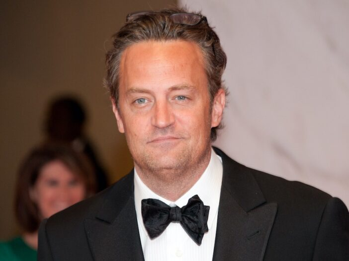close up of Matthew Perry smiling in a tuxedo with glasses on the top of his head