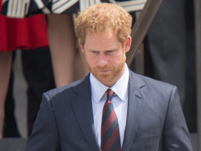 Close up of Prince Harry in a grey suit with red striped tie standing outside