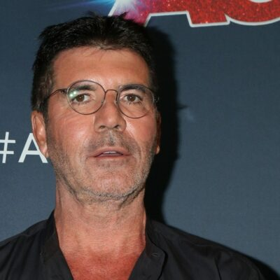 Close up of Simon Cowell wearing glasses and looking confused.