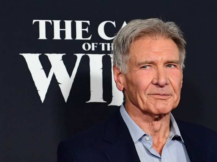 Close up shot of Harrison Ford looking to his right in a dark suit jacket and blue shirt on a black