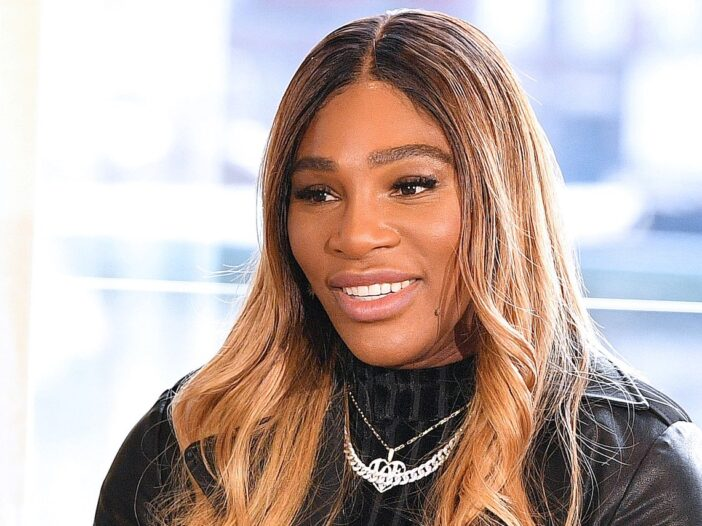 close up shot of Serena Williams smiling in a black top with silver jewelry