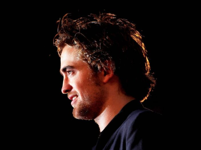 Close up side profile of Robert Pattinson in a dark suit at a Twilight premiere