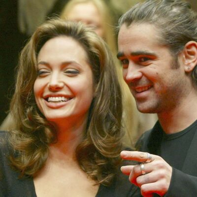 Colin Farrell smiling and pointing while saying something to Angelina Jolie