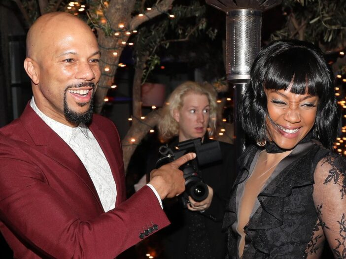 Common in a maroon suit smiles and points at a smiling Tiffany Haddish in a black lacy dress