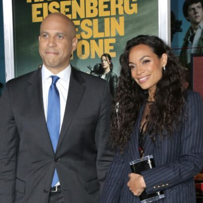 Cory Booker, in a suit, poses with Rosario Dawson at the premiere of Zombieland Double Tap