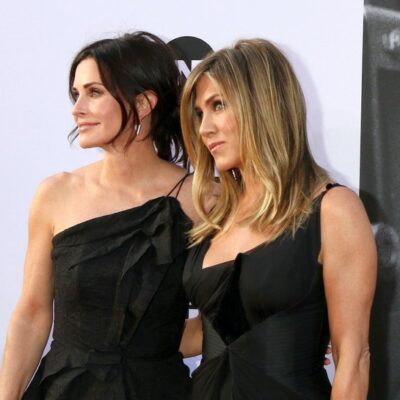 Courteney Cox smiles in a black dress with Jennifer Aniston in a black dress