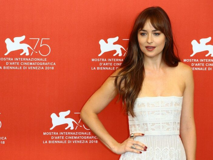 Dakota Johnson smiling with hand on hip in a white dress