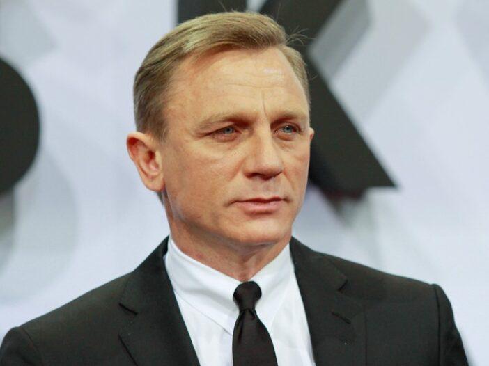 Daniel Craig looking serious in a black tuxedo.