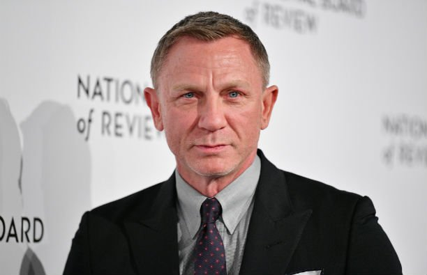 Daniel Craig wearing a dark suit with a light gray shirt on the red carpet.