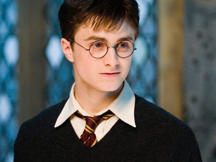 Daniel Radcliffe as Harry Potter looks to his left in a Hogwarts uniform
