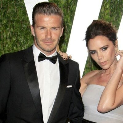 David and Victoria Beckham together in formal wear in front of a green background
