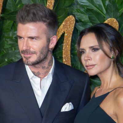 David Beckham grinning in a grey suit with wife Victoria Beckham in a dark dress in front of leaves