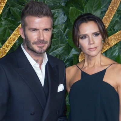 David Beckham in a suit on the left, Victoria Beckham in a blue dress on the right.
