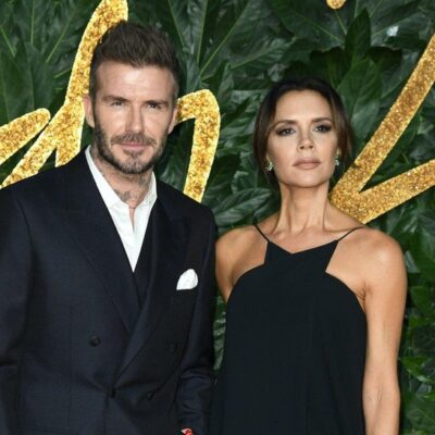 David Beckham in a suit standing with Victoria Beckham in a black dress