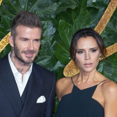 David Beckham smiling in a suit with Victoria Beckham in a black dress