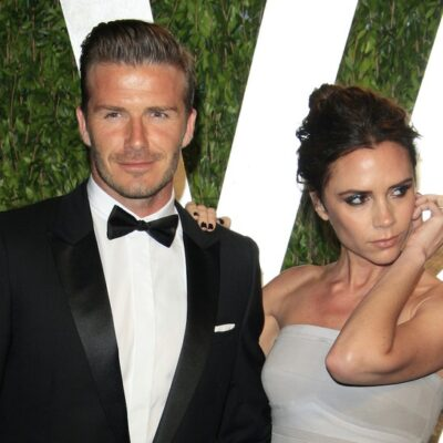 David Beckham smiling in a tuxedo with Victoria Beckham in a grey dress