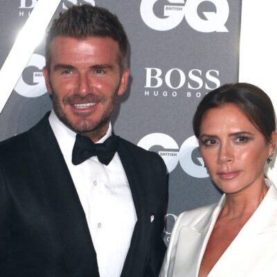 David Beckham smiling in a tuxedo with wife Victoria Beckham in a white blazer