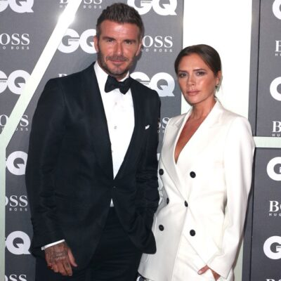 David Beckham wearing a black suit standing with his wife, Victoria, who's wearing a white suit