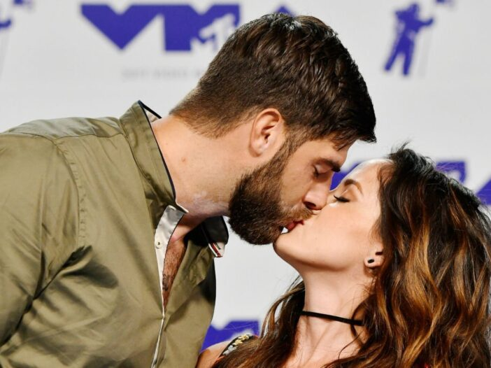 David Eason wearing an olive jacket kissing Jenelle Evans on the red carpet