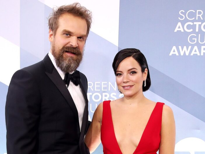 David Harbour in a tux and Lily Allen in a red dress with their arms around one another smiling