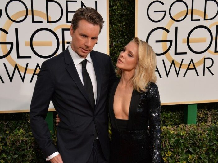 Dax Shepard on the right in a tux, standing with Kristen Bell in a low-cut black dress.