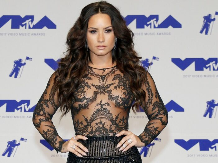 Demi Lovato in a sheer black top and sparkly black skirt