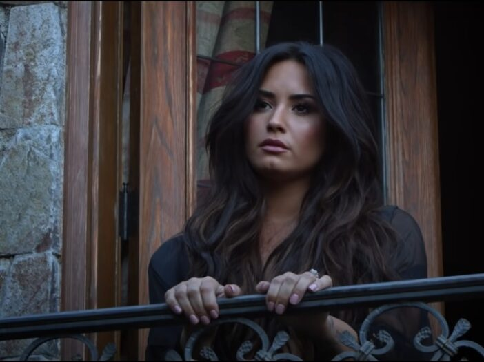 Demi Lovato wearing a sheer black robe on the set of her music video Tell Me You Love Me