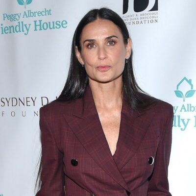 Demi Moore looking at the camera while dressed in a closed maroon jacket