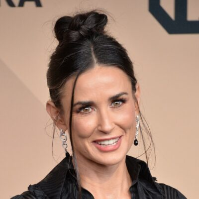 Demi Moore smiling in a black dress.