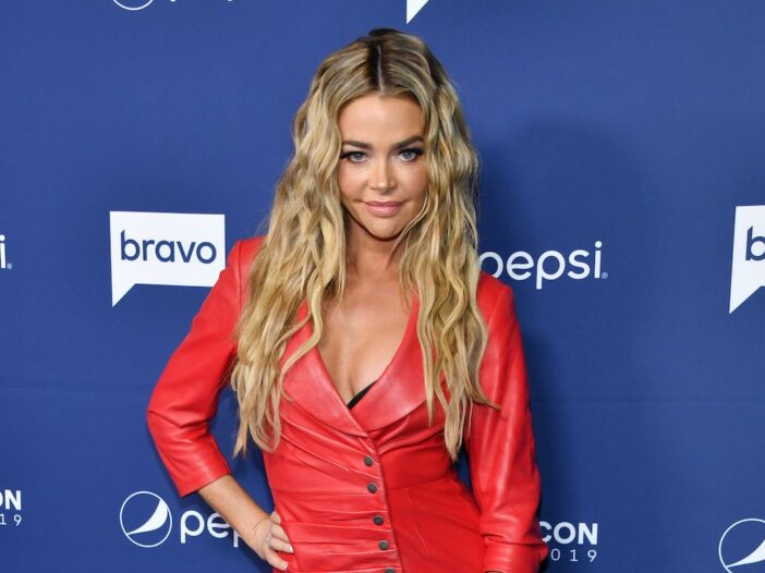 Denise Richards smiles in a red leather outfit against a blue background