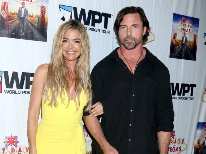 Denise Richards, wearing a yellow dress, standing with her husband Aaron Phypers at a premiere