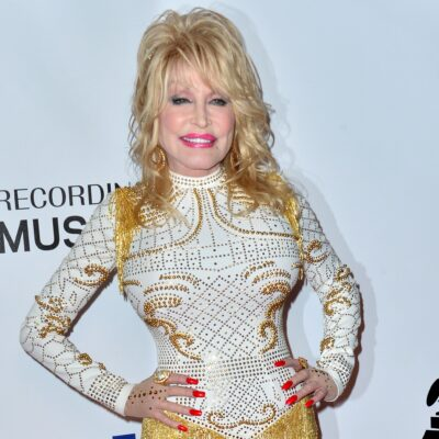 Dolly Parton in a sparkling gold and white dress.