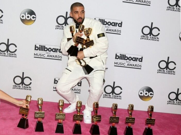 Drake wearing a white tux and holding several awards at the Billboard Music Awards